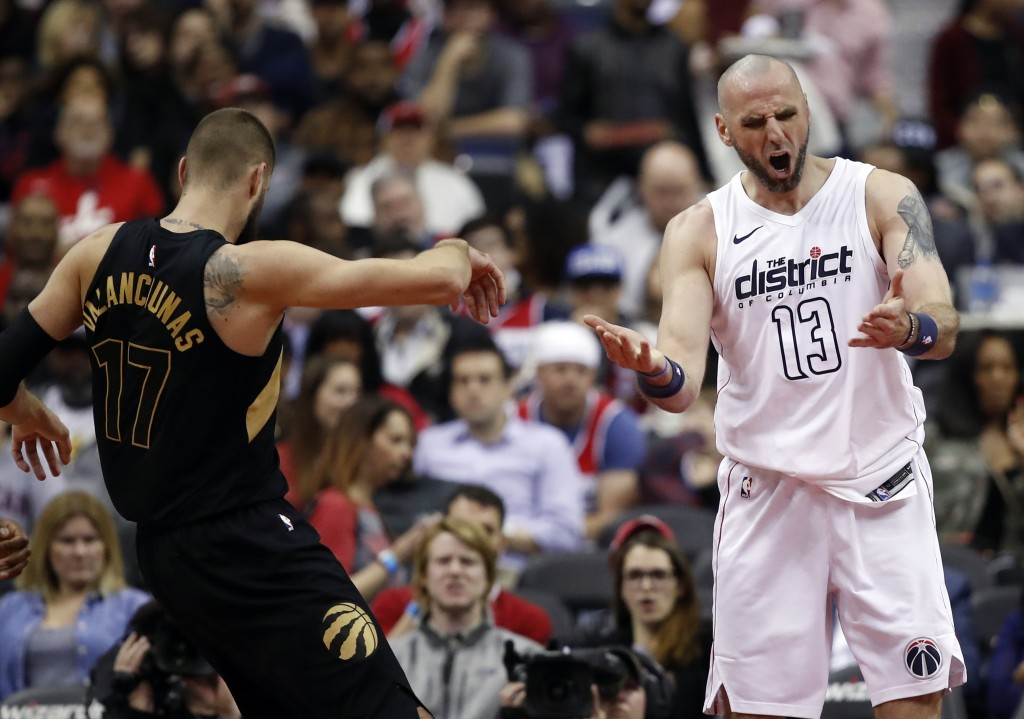 Washington Wizards center Marcin Gortat, right, reacts after being called for a foul on Toronto Raptors center Jonas Valanciunas during the second hal...