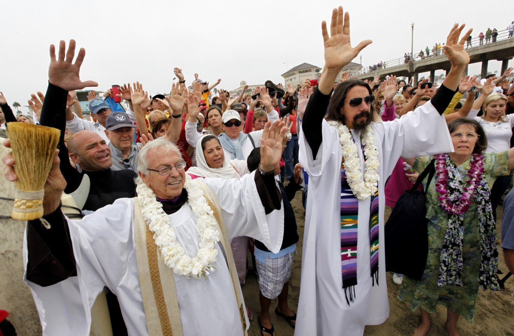 FILE - In this Sunday, Oct. 3, 2010, file photo, Rev. Christian Mondor, left with Rev. Matt Munoz, center, offers a prayer to surfers during the Bless...