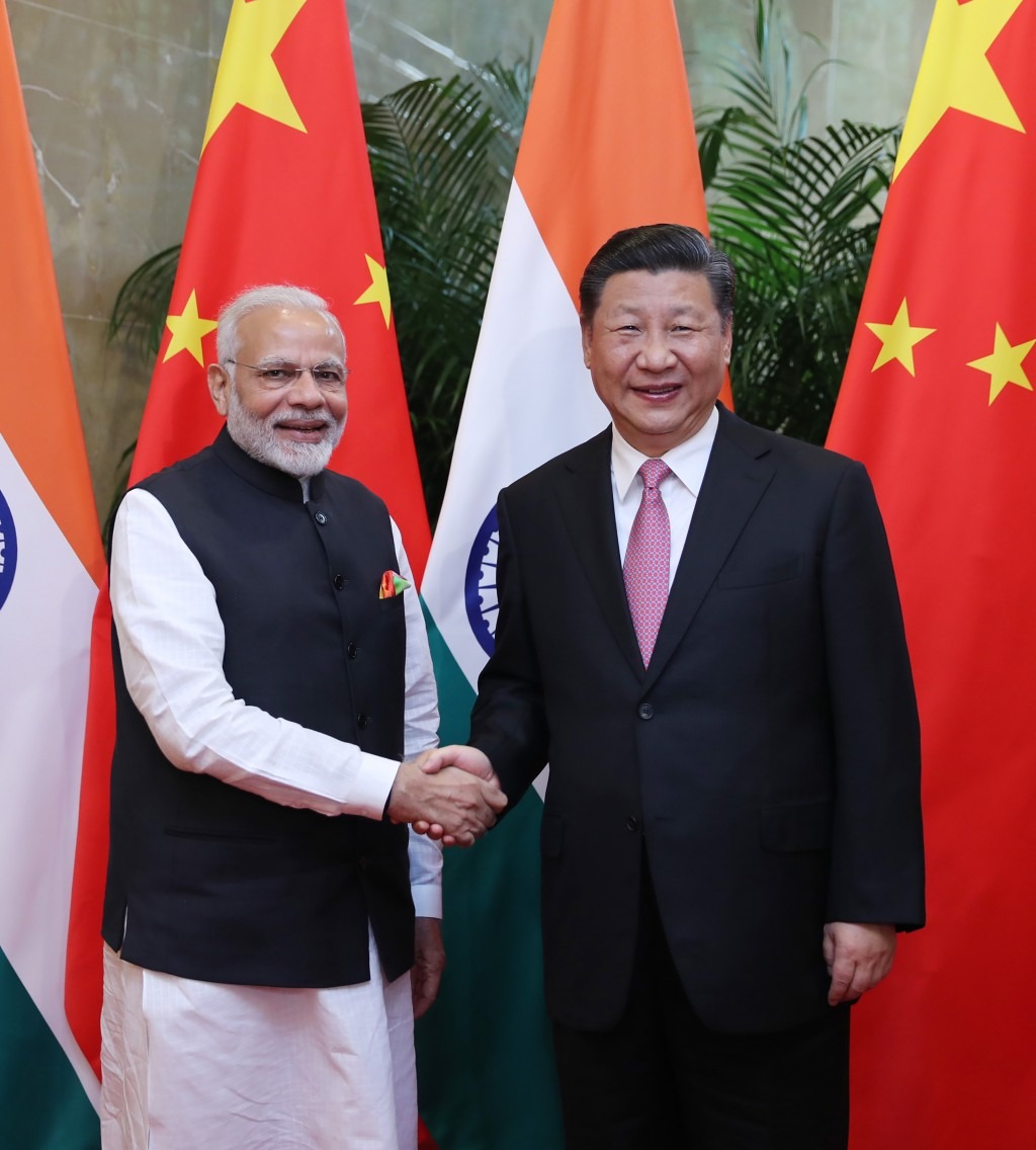 In this photo released by China's Xinhua News Agency, Indian Prime Minister Narendra Modi, left, poses with Chinese President Xi Jinping for a photo a...