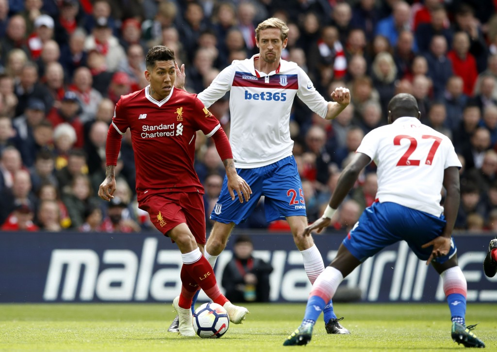 Liverpool's Roberto Firmino, left, and Stoke City's Badou Ndiaye, right, face off with Peter Crouch behind, during the English Premier League soccer m...