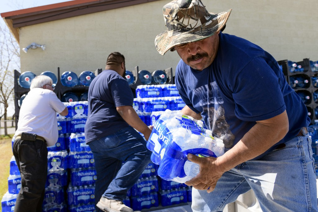 Nicolas Cuevas, right, and others load up plastic water bottles to distribute to members of the Yerington Paiute tribe after their weekly water delive...