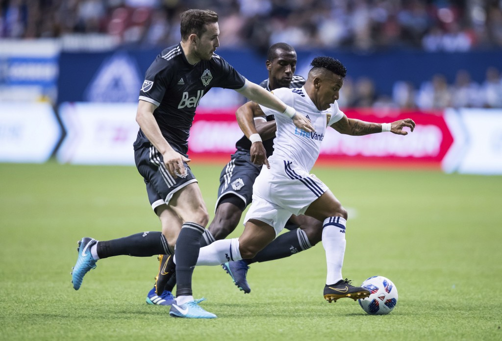 Real Salt Lake's Joao Plata, front right, controls the ball past Vancouver Whitecaps' Jordon Mutch, left, and Ali Ghazal, back, during the first half ...