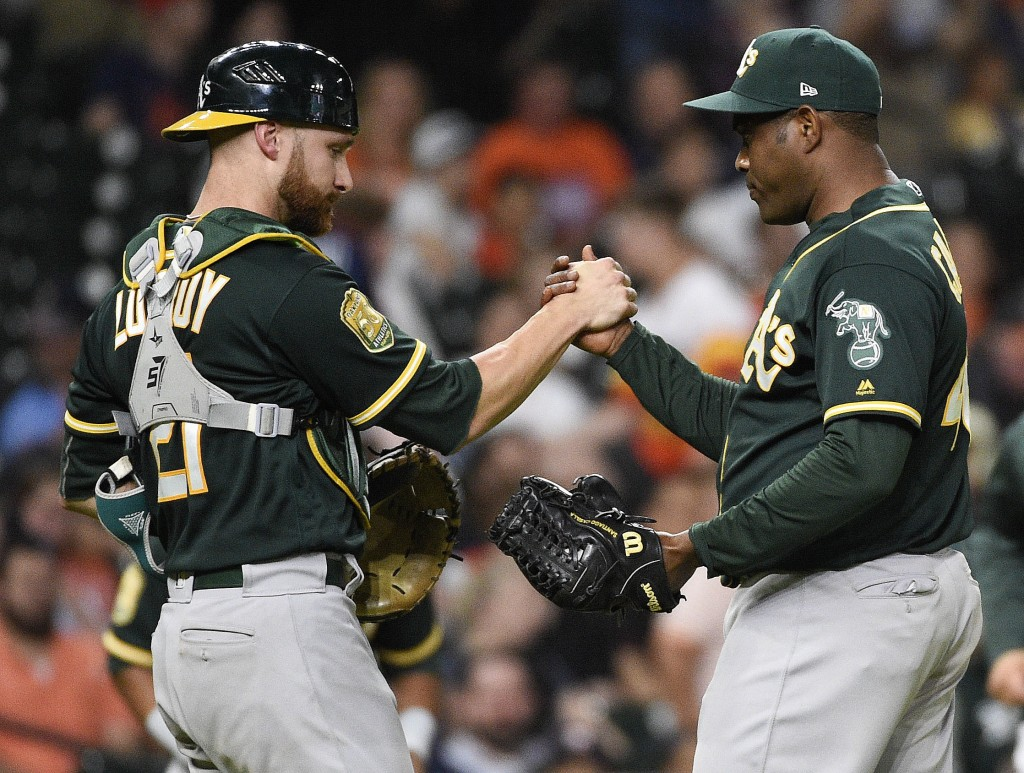 Oakland Athletics relief pitcher Santiago Casilla, right, and catcher Jonathan Lucroy clasp hands after the team's 8-1 win over the Houston Astros in ...