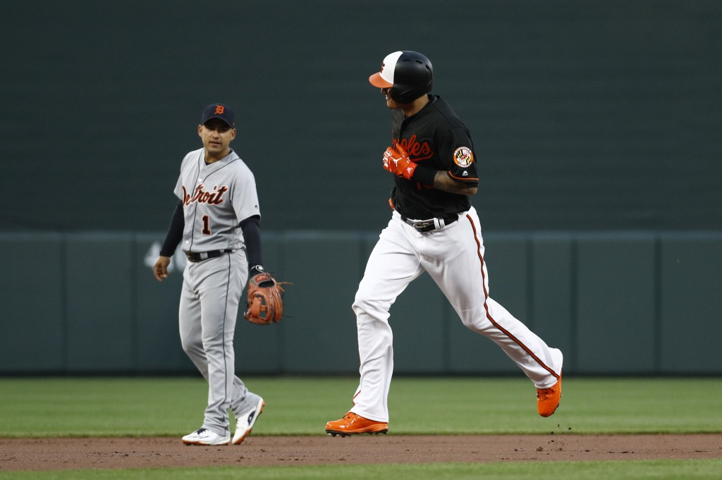 Baltimore Orioles' Manny Machado, right, rounds the bases past Detroit Tigers shortstop Jose Iglesias after hitting a solo home run during the first i...