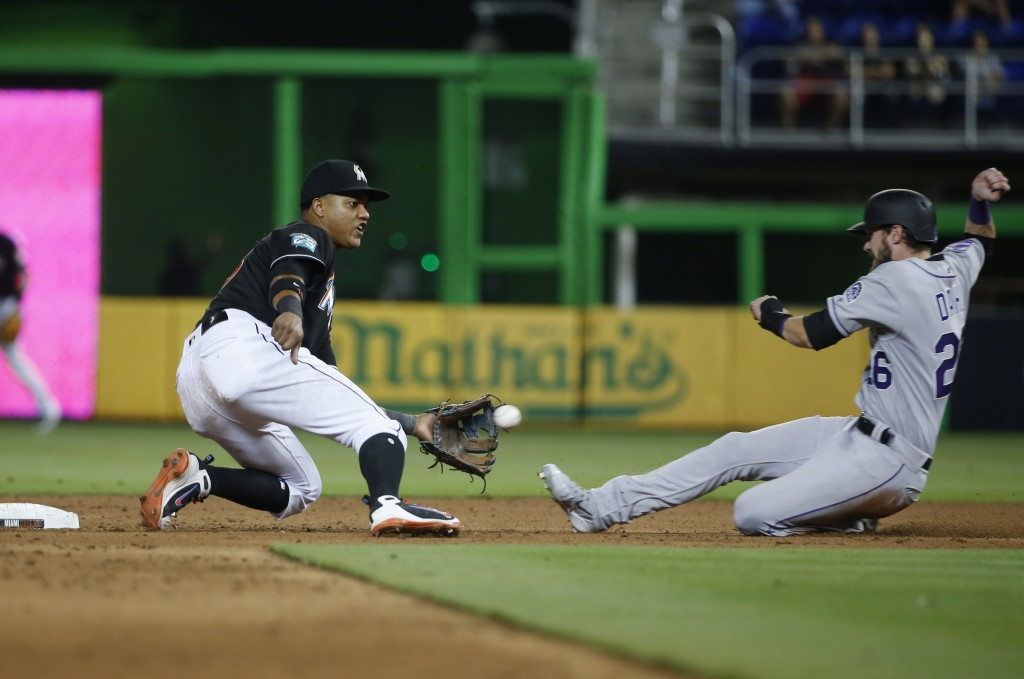 Miami Marlins second baseman Starlin Castro, left, prepares to tag Colorado Rockies' David Dahl (26) who was attempting to steal second during the six...