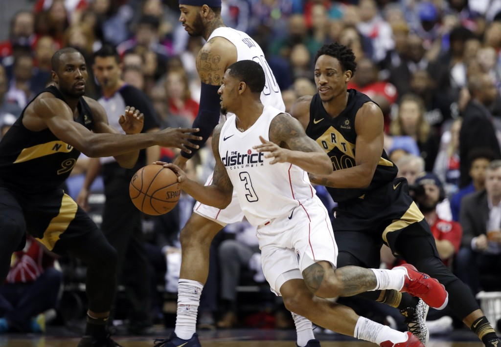 Washington Wizards guard Bradley Beal (3) tries to get away from Toronto Raptors guard DeMar DeRozan, right, during the first half of Game 6 of an NBA...