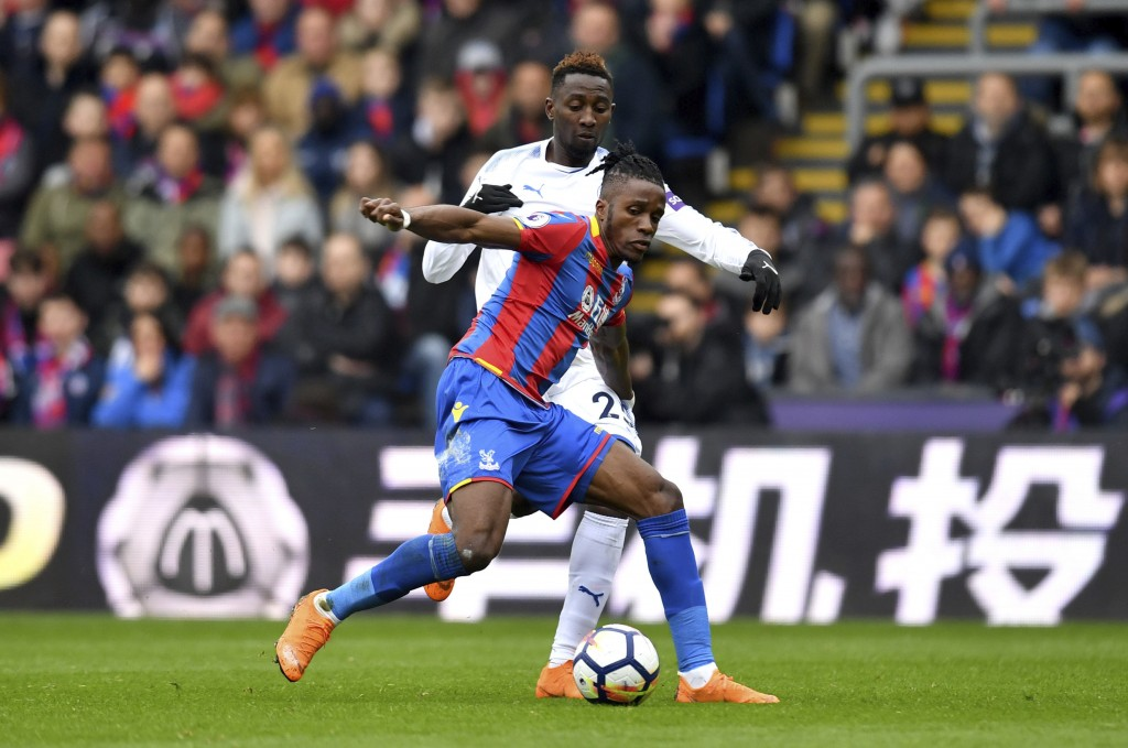 Crystal Palace's Wilfried Zaha, front, and Leicester City's Wilfred Ndidi battle for the ball during their English Premier League soccer match at Selh...
