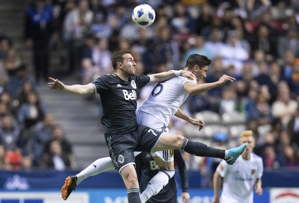 Vancouver Whitecaps' Jordon Mutch, left, and Real Salt Lake's Damir Kreilach battle for the ball during the first half of an MLS soccer match Friday, ...