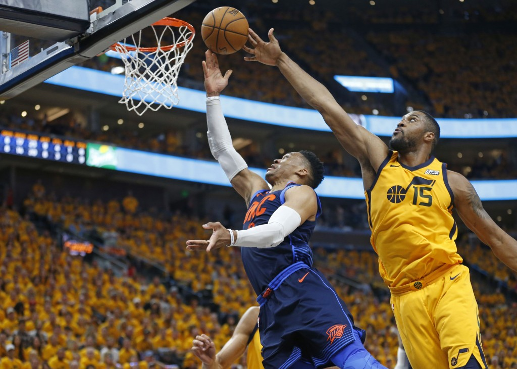 Utah Jazz forward Derrick Favors (15) defends against Oklahoma City Thunder guard Russell Westbrook during the first half of Game 6 in an NBA basketba...