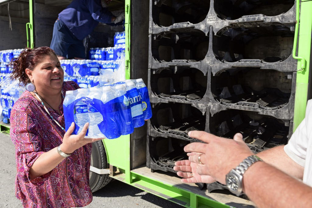 Yerington Paiute tribe chairman Laurie Thom helps offload water from a delivery truck on the outskirts of Yerington, Nev., Friday, April 27, 2018. Atl...