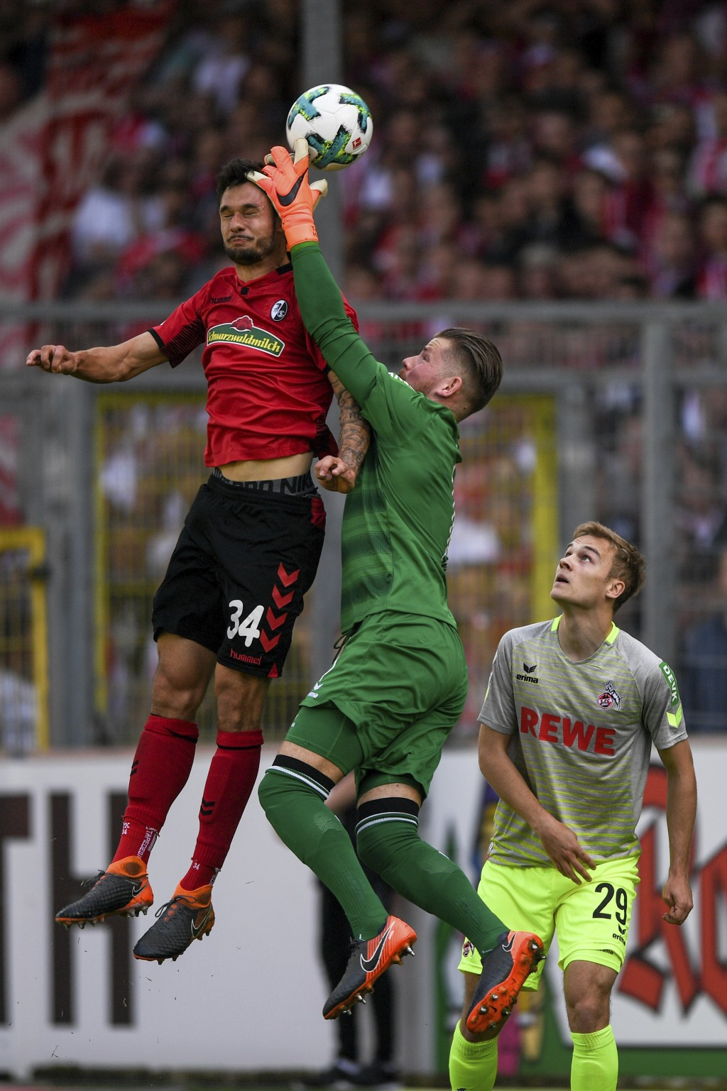 Cologne's goalie Timo Hornm center, and Freiburg's Tim Kleindienst, left, challenge for the ball while Cologne's Tim Handwerker looks on during the Ge...