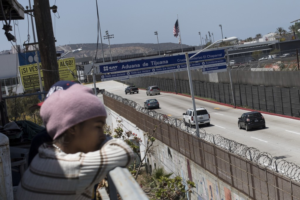 A migrant child from Honduras looks across the US-Mexico Border from Tijuana, Mexico, Friday, April 27, 2018. Close to 200 migrants from Central Ameri...