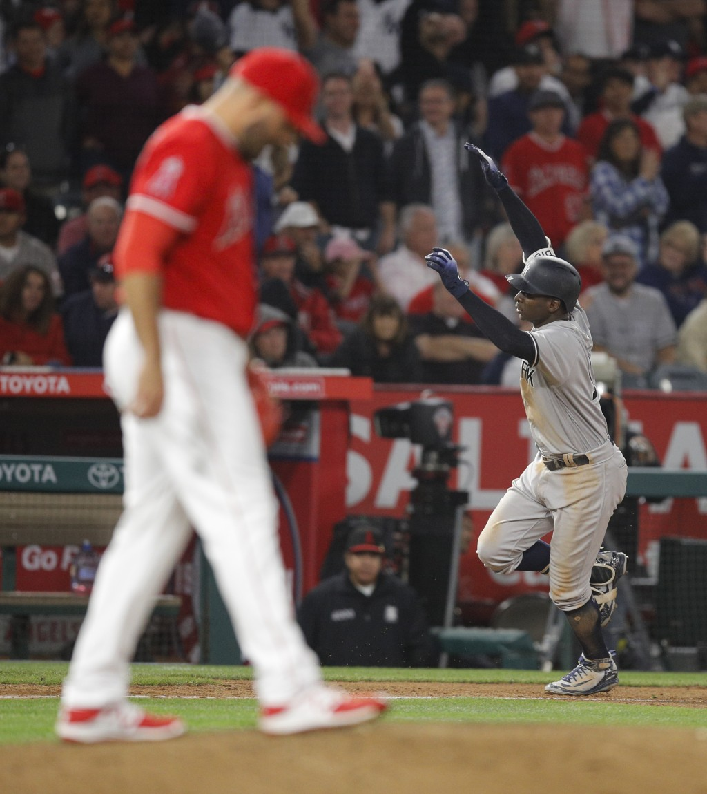 New York Yankees' Didi Gregorius, right, celebrates his home run against Los Angeles Angels relief pitcher Blake Parker, foreground, during the 10th i...