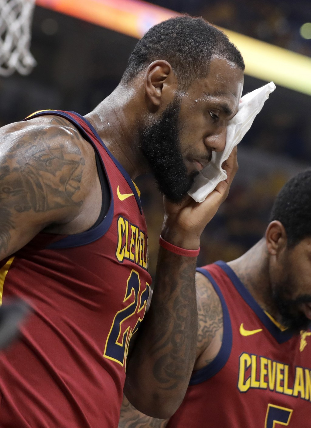Cleveland Cavaliers' LeBron James holds a cloth to a cut above his eye after being injured on a drive to the basket during the first half of Game 6 of...