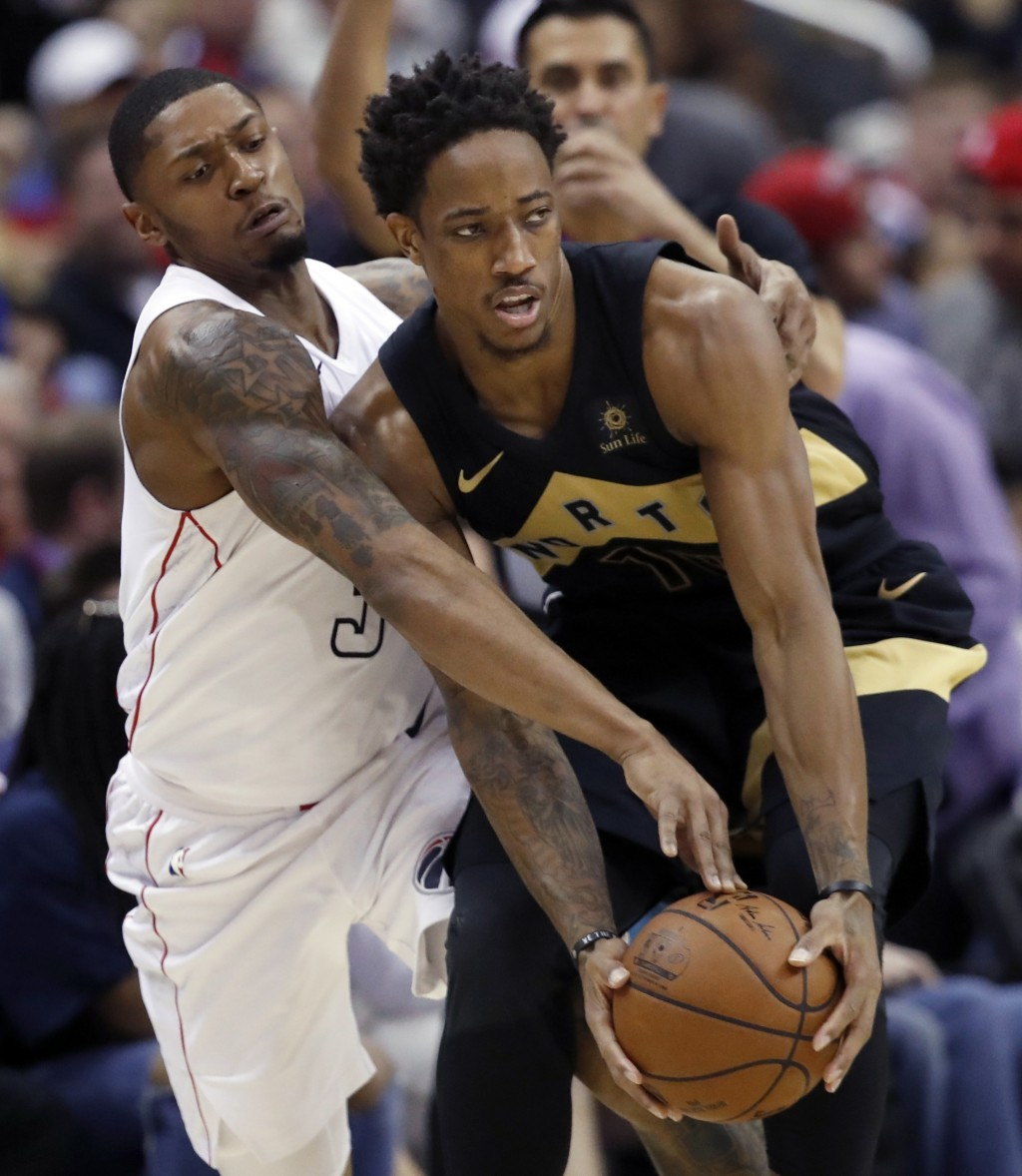 Washington Wizards guard Bradley Beal, left, reaches for the ball in the hands of Toronto Raptors guard DeMar DeRozan during the second half of Game 6...