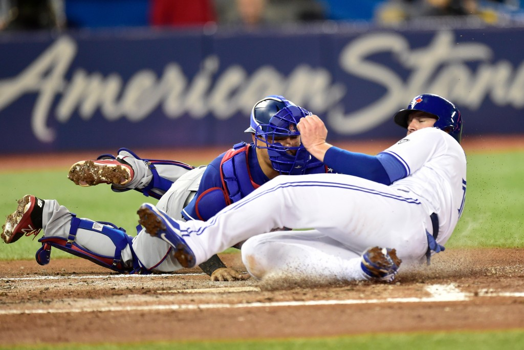 Toronto Blue Jays' Justin Smoak (14) is out at home plate on a tag by Texas Rangers catcher Juan Centeno during the first inning of a baseball game Fr...