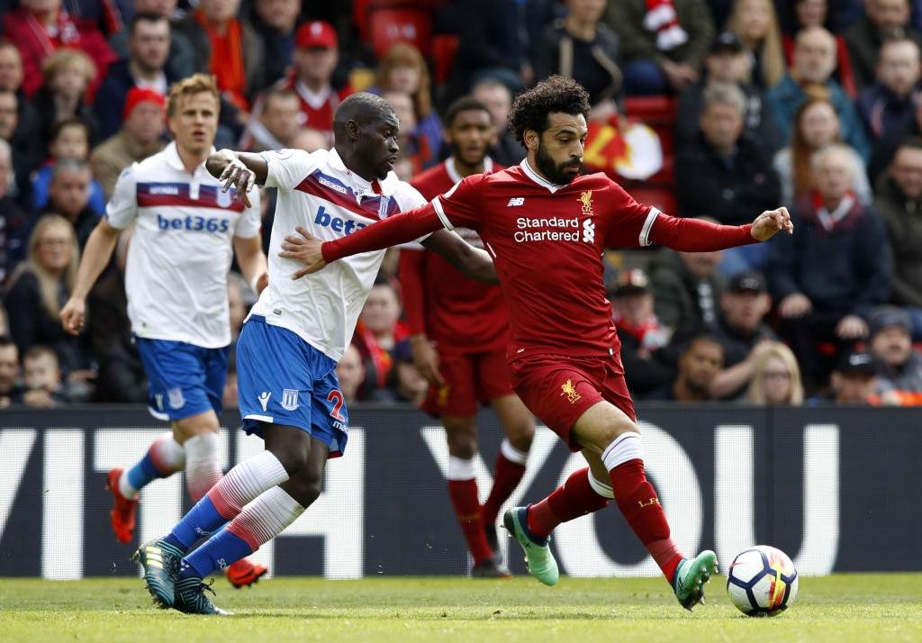 Stoke City's Badou Ndiaye, left and Liverpool's Mohamed Salah vie for the ball, during the English Premier League soccer match between Liverpool and S...