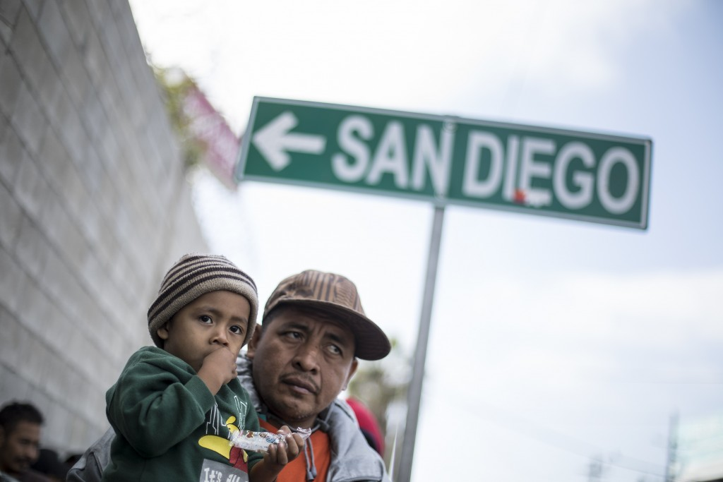 A father and his son await tutorship by immigration lawyers in Tijuana, Mexico, Friday, April 27, 2018. Close to to 200 migrants from Central America,...