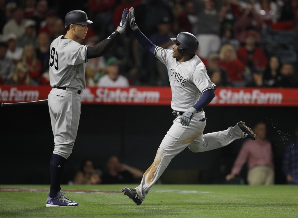 New York Yankees' Miguel Andujar, right, is greeted by Aaron Judge after scoring on a sacrifice fly by Aaron Hicks during the fifth inning of a baseba...