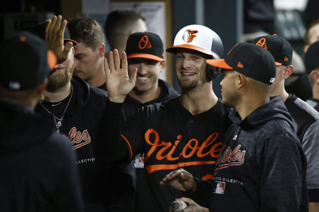 Baltimore Orioles' Caleb Joseph high-fives teammates in the dugout after scoring on Jace Peterson's double during the sixth inning of a baseball game ...
