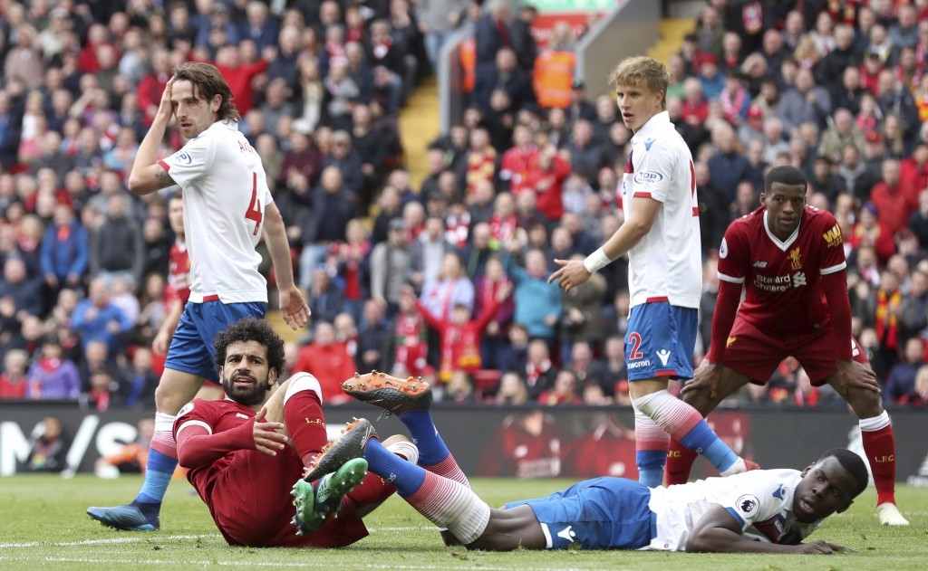 Liverpool's Mohamed Salah foreground left, reacts after a tackle, during the English Premier League soccer match between Liverpool and Stoke City, at ...