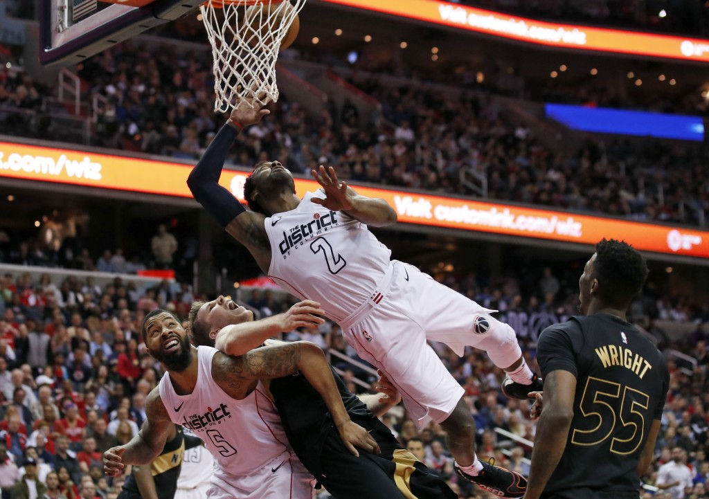 Washington Wizards guard John Wall (2) shoots as he falls over Washington Wizards forward Markieff Morris (5) and Toronto Raptors center Jakob Poeltl ...