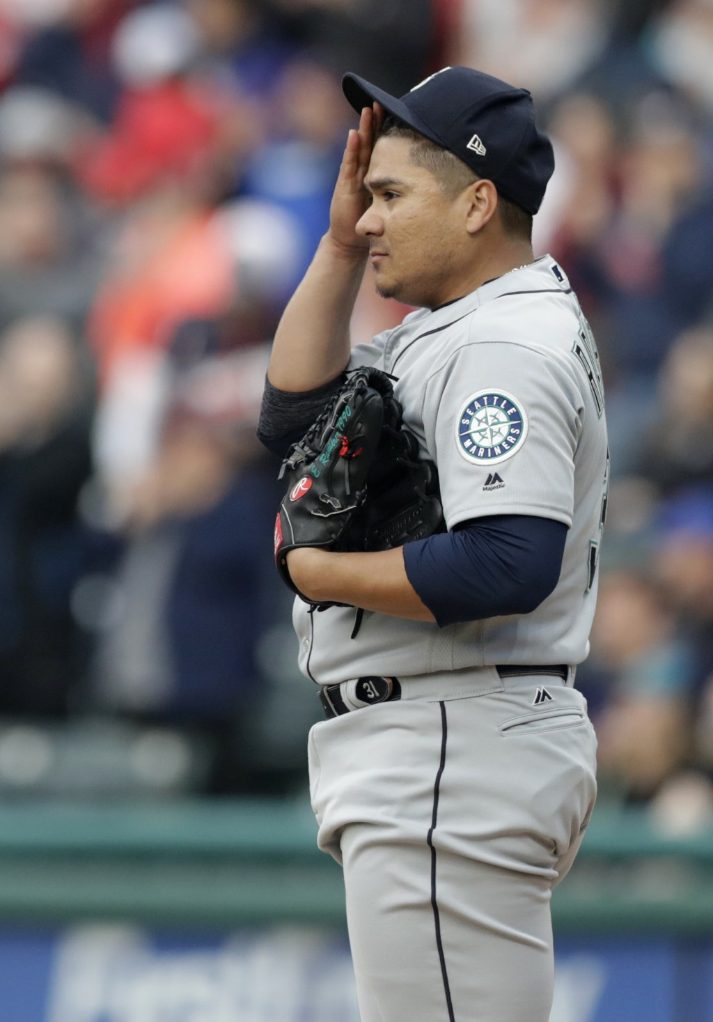 Seattle Mariners starting pitcher Erasmo Ramirez wipes his forehead as he waits for Cleveland Indians' Michael Brantley to run the bases on a solo hom...