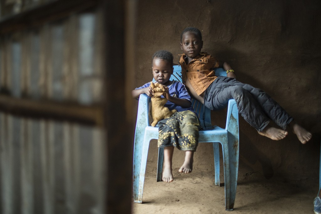 In this April 16, 2018 photo, three-year-old Shukri Muhamed, left, and her brother Ibrahim, 6, share a chair at their home at the Kakuma Refugee Camp ...