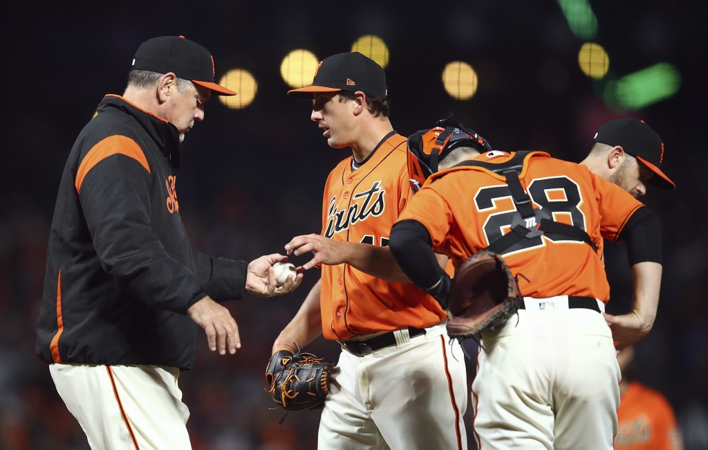 San Francisco Giants manager Bruce Bochy, left, removes pitcher Derek Holland, second from left, after Los Angeles Dodgers' Hyun-Jin Ryu hit a two-run...