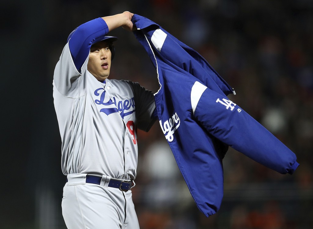 Los Angeles Dodgers' Hyun-Jin Ryu puts on a jacket after hitting a two-run double off San Francisco Giants pitcher Derek Holland during the fourth inn...
