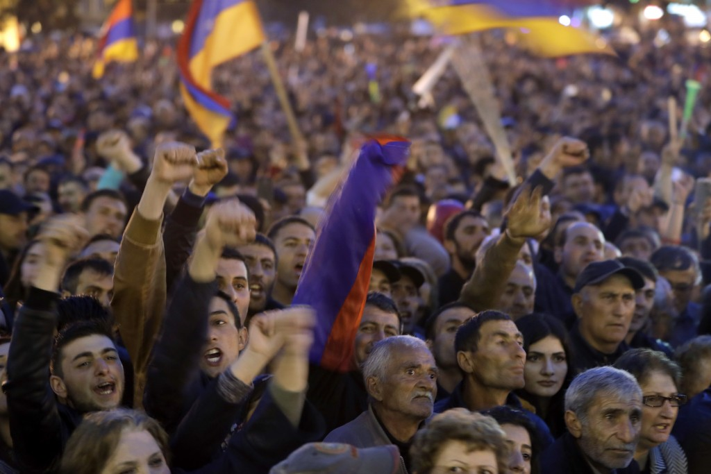 Protesters react while listening to their leader Nikol Pashinian in the town of Gyumri, Armenia, Friday, April 27, 2018. Armenian opposition leader Ni...