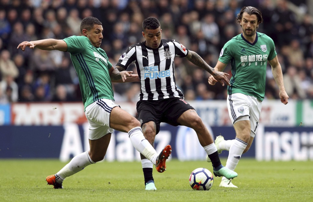 Newcastle United's Kenedy, centre, battles for the ball with West Bromwich'sJake Livermore, left and Jay Rodriguez the English Premier League soccer m...