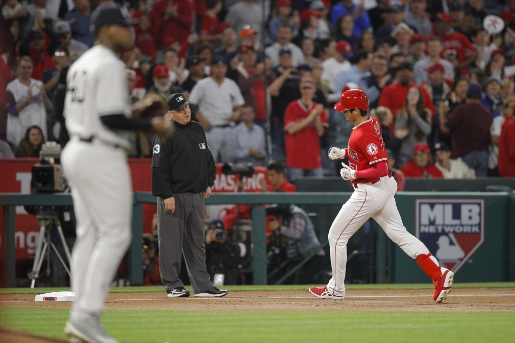 Los Angeles Angels' Shohei Ohtani, right, of Japan, rounds the bases after hitting a home run off New York Yankees starting pitcher Luis Severino, for...