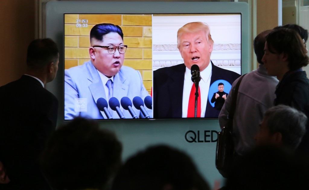 FILE - In this April 21, 2018 file photo, People watch a TV screen showing file footage of U.S. President Donald Trump, right, and North Korean leader...
