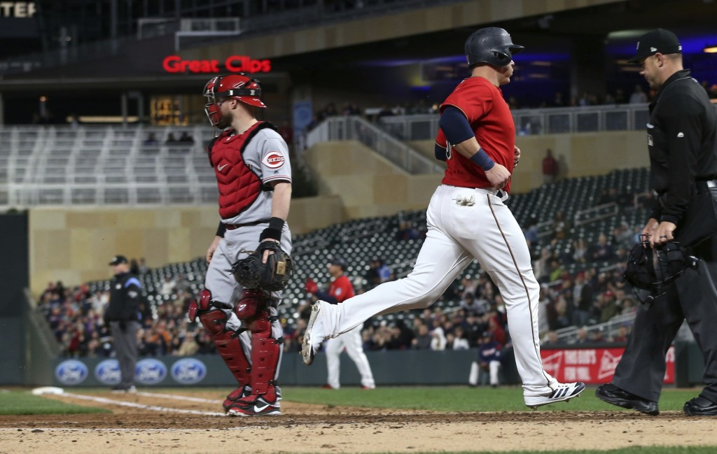 Minnesota Twins' Logan Morrison, right, scores on an RBI-double by Robbie Grossman off Cincinnati Reds' pitcher Kevin Shackelford in the third inning ...