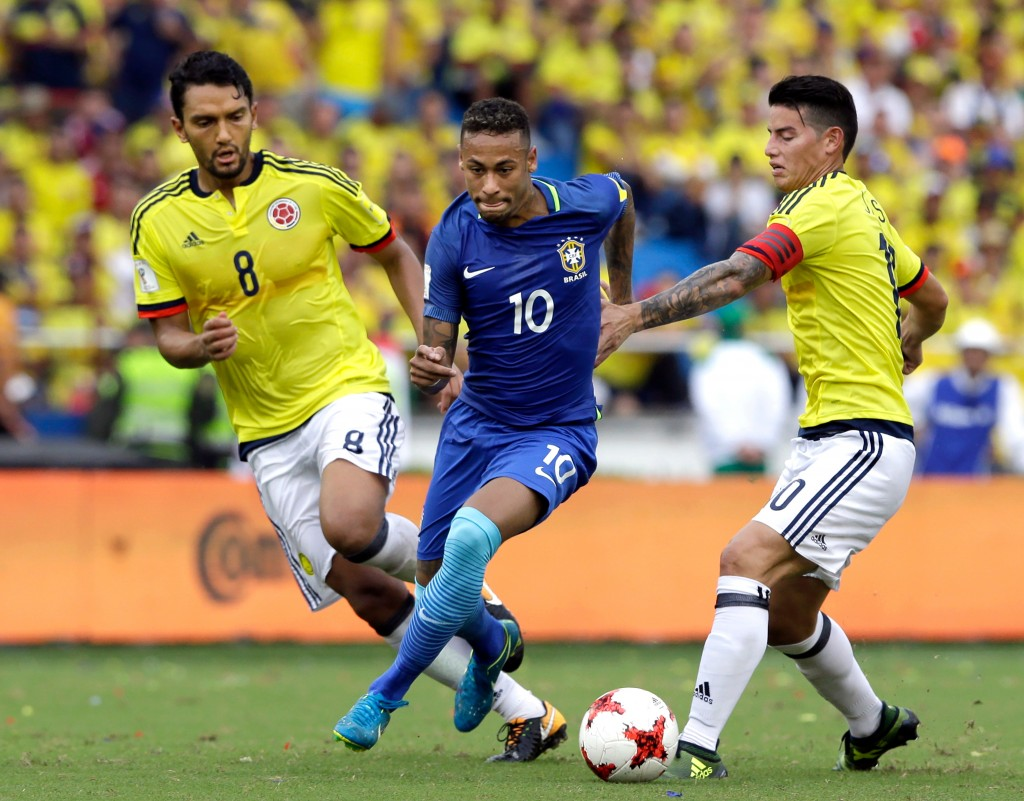 FILE - In this Tuesday, Sept. 5, 2017 filer, Brazil's Neymar, center, fights for the ball with Colombia's Abel Aguilar, left, and James Rodriguez, dur...