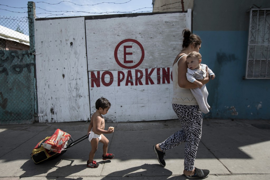 A Honduran migrant who is traveling with a caravan of Central American migrants walks with her two children to a shelter in Tijuana, Mexico, Wednesday...