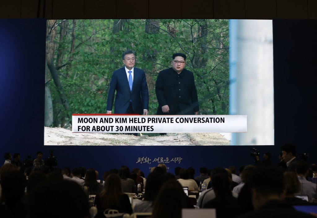 In this April 27, 2018 photo, Journalists watch a huge screen shows live video of North Korean leader Kim Jong Un and South Korean President Moon Jae-...