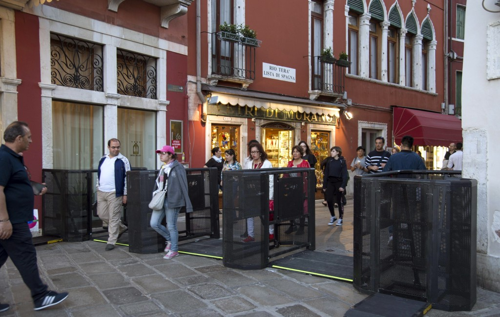 In this photo taken on Friday, April 27, 2018, people walk through gates in Venice, Italy. Venice has resorted to installing gates at the ends of two ...