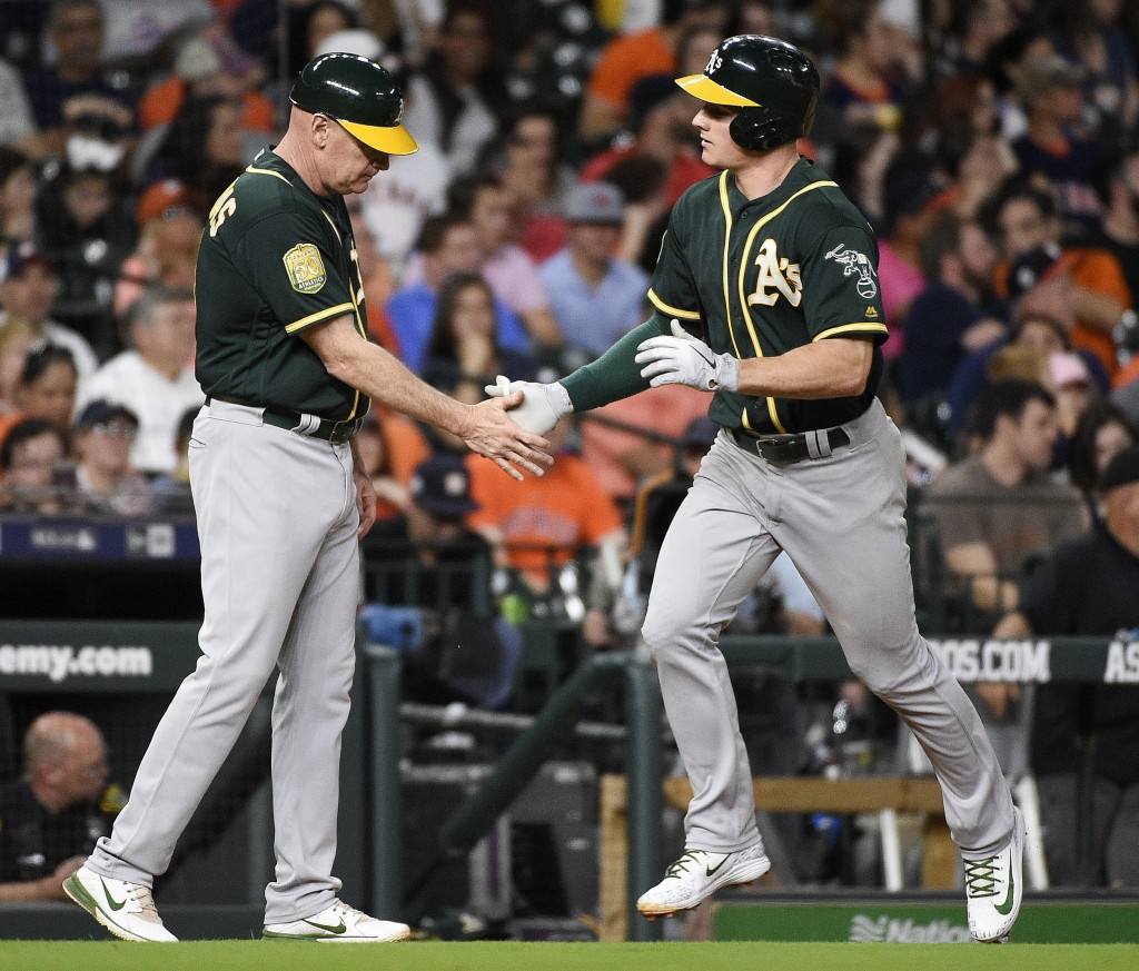 Oakland Athletics' Matt Chapman, right, shakes hands with third base coach Matt Williams after hitting a solo home run off Houston Astros starting pit...