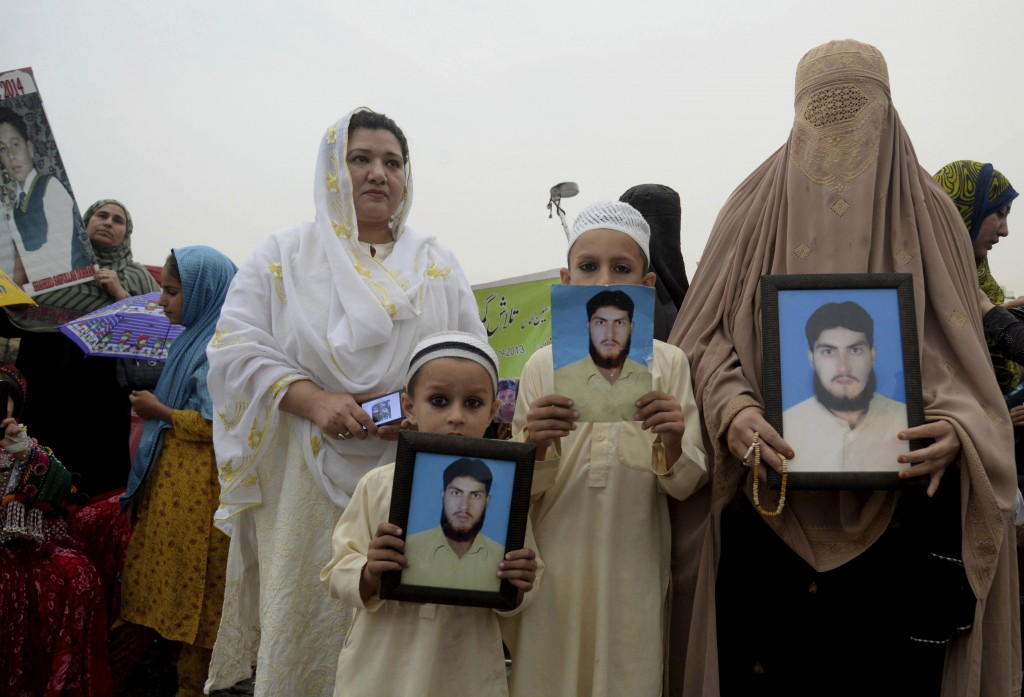 FILE - In this Sunday, April 8, 2018 file photo, a Pashtun family from a Pakistani tribal area display pictures of a missing family member during a Pa...