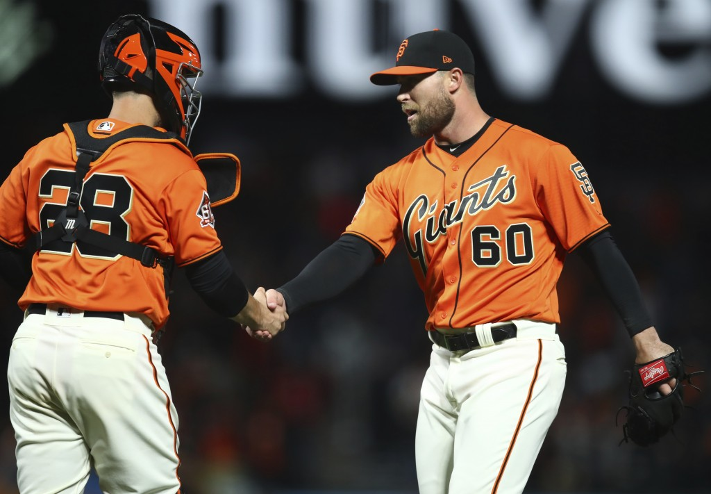 San Francisco Giants pitcher Hunter Strickland, right, and catcher Buster Posey celebrate the 6-4 win over the Los Angeles Dodgers at the end of a bas...