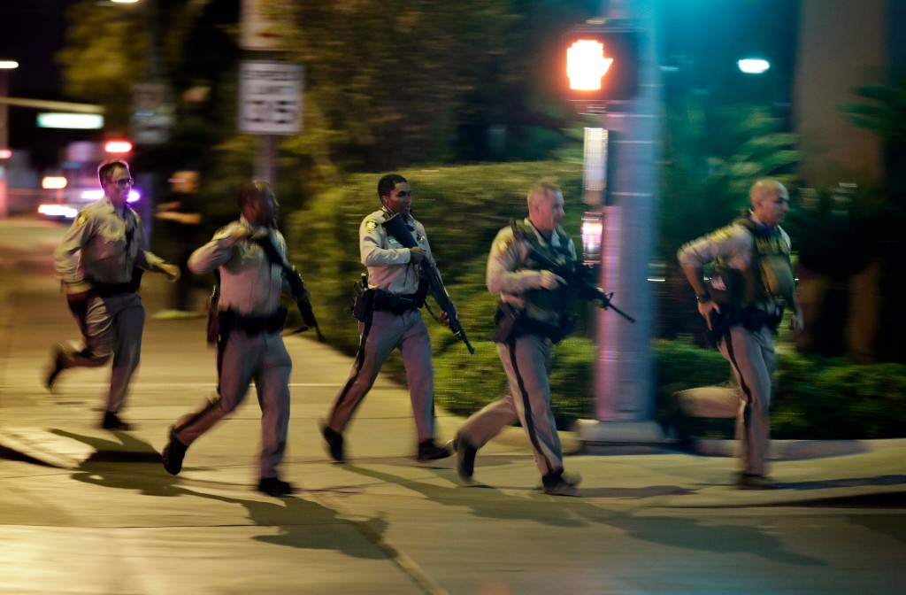 FILE - In this Sunday, Oct. 1, 2017 file photo, police run toward the scene of a shooting near the Mandalay Bay resort and casino on the Las Vegas Str...