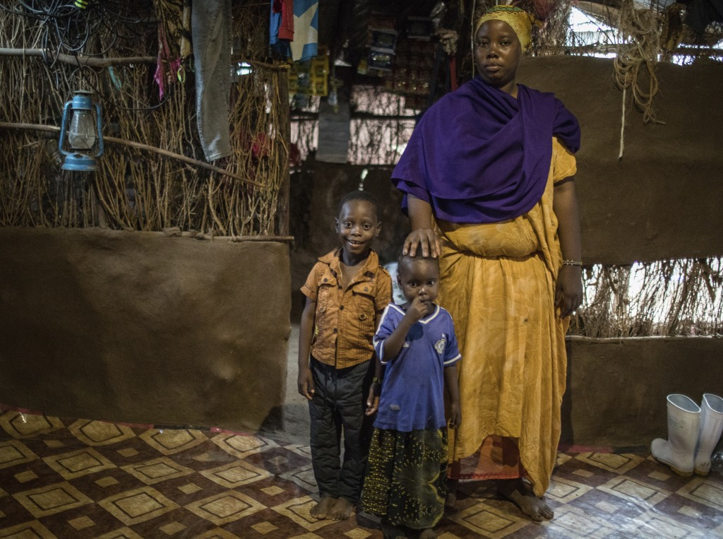 In this April 16, 2018 photo, Saido Muhina Khamis stands in her home with her children, Ibrahim Muhamed, 6, left, and his sister, Shukri, 3, at the Ka...