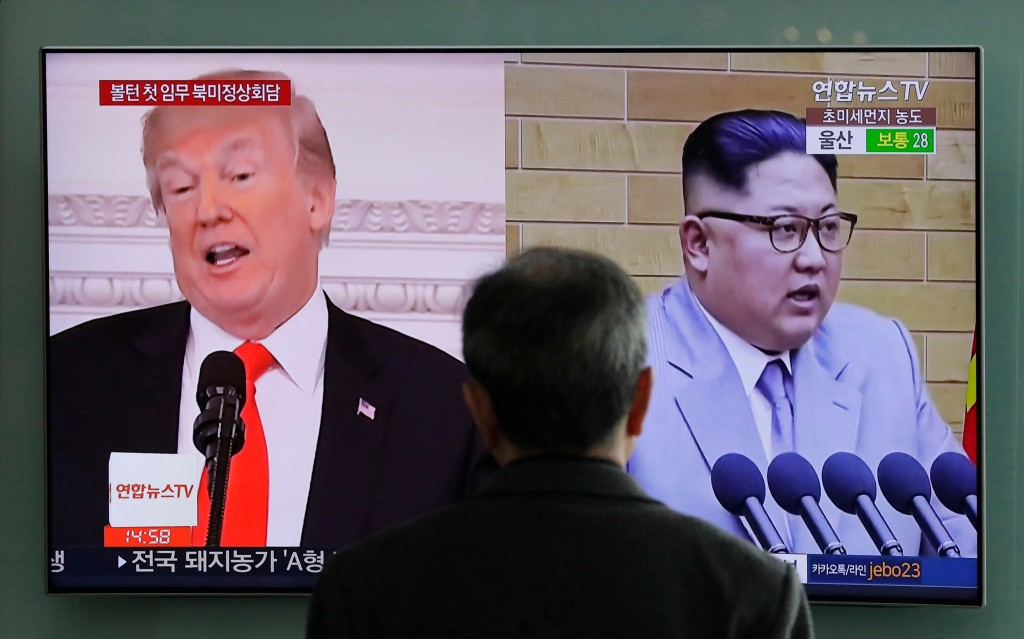 FILE - In this March 27, 2018 file photo, A man watches a TV screen showing file footages of U.S. President Donald Trump, left, and North Korean leade...