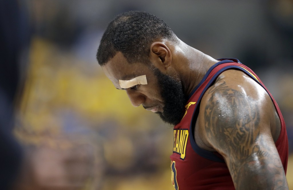 Cleveland Cavaliers' LeBron James remains in the game after sustaining a cut above his left eye on a drive to the basket during the first half of Game...