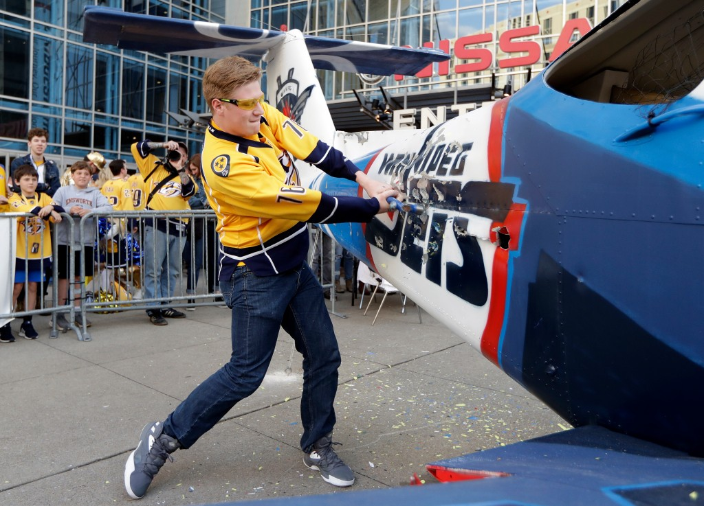 Nashville Predators fan Devin Bradshaw takes a turn beating on a plane painted with the Winnipeg Jets logo and colors outside of Bridgestone Arena bef...