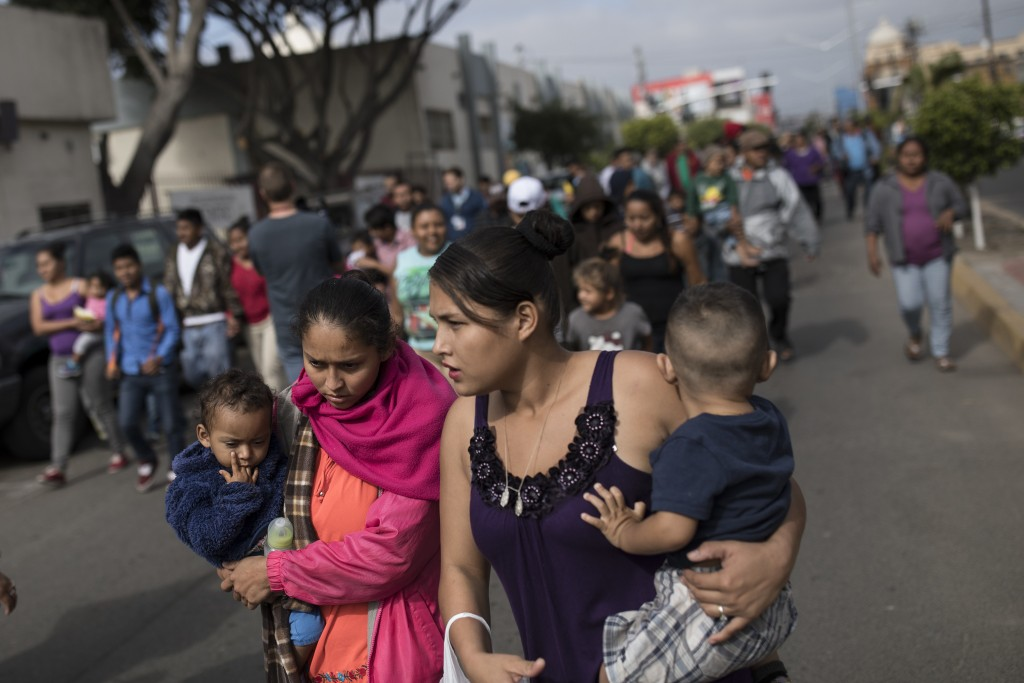 Migrants walk to the place where they will be meeting with lawyers, seeking to enter the United States from Tijuana, Mexico, Friday, April 27th 2018. ...