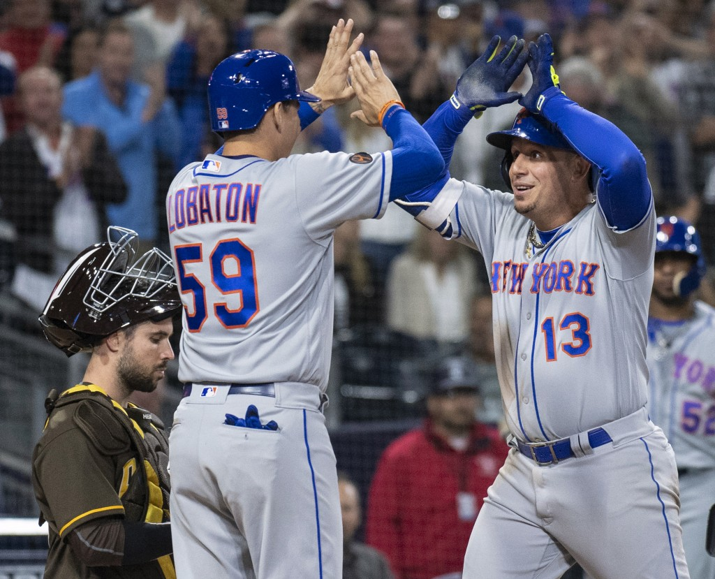 New York Mets' Asdrubal Cabrera, right, celebrates his three-run home run with Jose Lobaton as San Diego Padres catcher Austin Hedges waits during the...