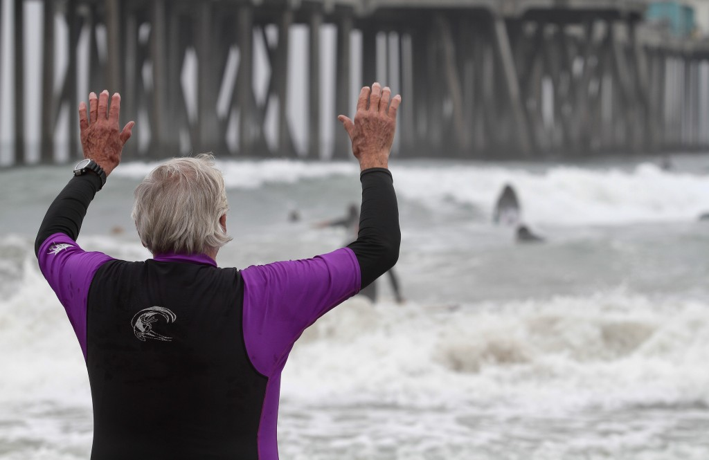 FILE - In this Oct. 3, 2010, file photo, Rev. Christian Mondor offers a prayer to surfers as they take to the waves during the Blessing of the Waves c...